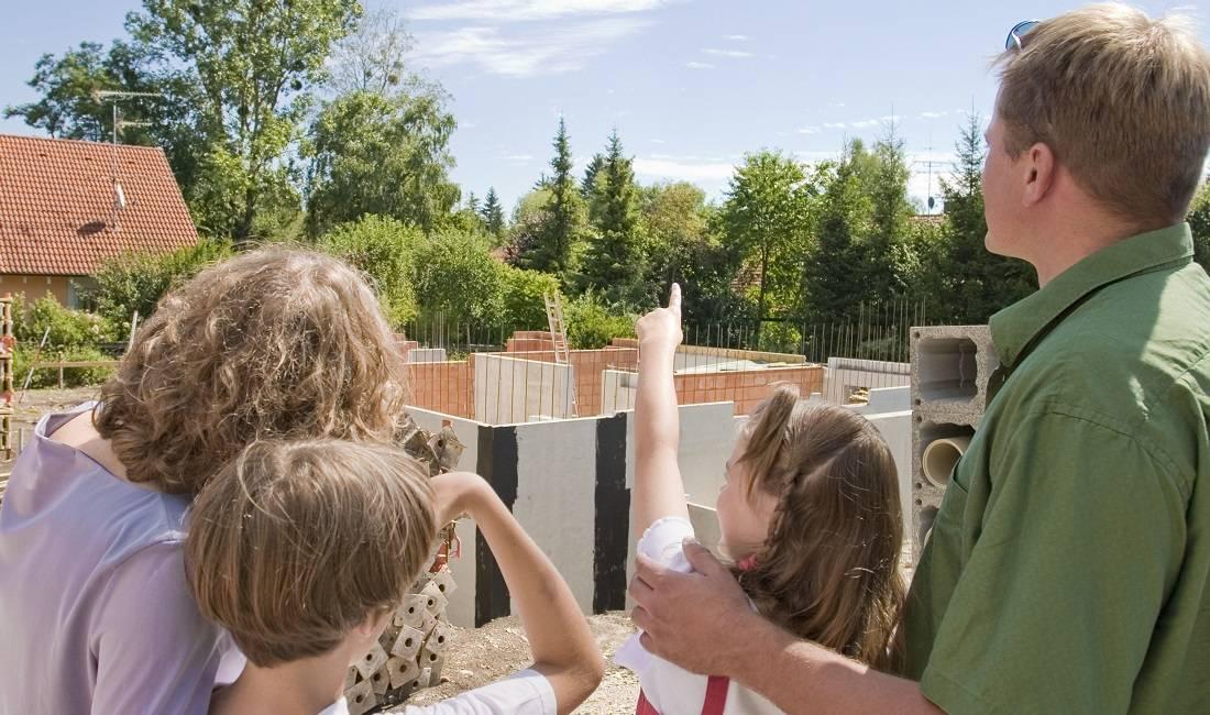 Eine Familie begutachtet die Baustelle ihres neuen Eigenheims